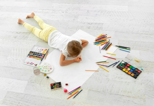 Mała dziewczynka rysunek na papierze, leżąc na podłodze