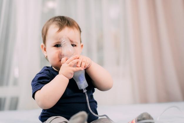 Mała dziewczynka sama trzymająca maskę nebulizatora, wykonująca inhalację i leczona