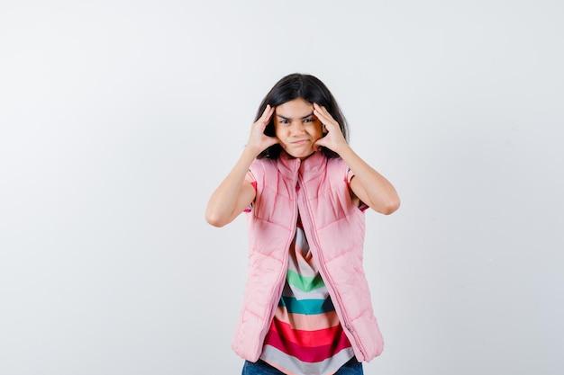 Mała dziewczynka ściskając głowę rękami w t-shirt, kamizelkę puchową, dżinsy i patrząc zirytowany, widok z przodu.