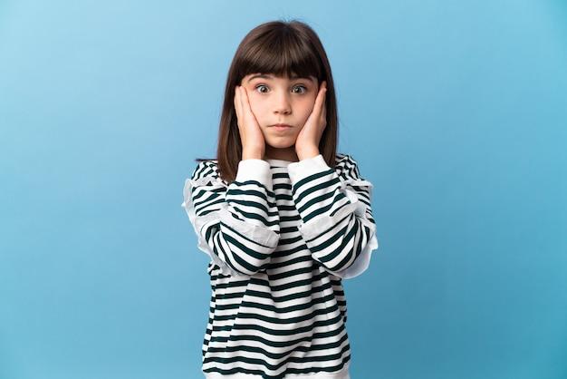 Mała dziewczynka sfrustrowana izolowaną ścianą i zakrywająca uszy