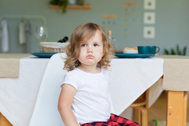Mała dziewczynka siedząca i smutny, emocjonalny portret.