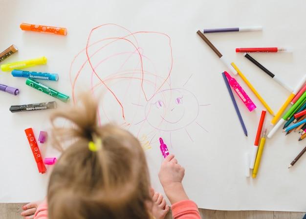 Mała dziewczynka siedząca na podłodze lubi kreatywność rysując ołówkami kolorując obrazki w albumach. widok z góry