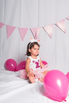 Mała dziewczynka siedząca na podłodze z koroną z rogu jednorożca wykonująca gesty.