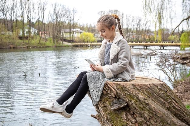 Mała dziewczynka, siedząca nad rzeką, sprawdza telefon i nie zwraca uwagi na otaczającą przyrodę.
