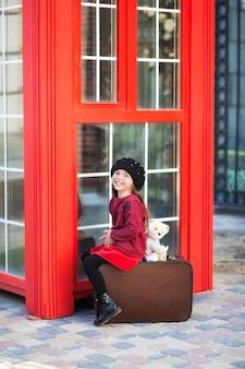 Mała dziewczynka siedzi blisko czerwonej budki telefonicznej z puszystym koralikiem w berecie. mała dziewczynka siedzi na walizce z misiem. czerwona budka telefoniczna w londynie. zakończenie portret twarzy małej dziewczynki dziecko