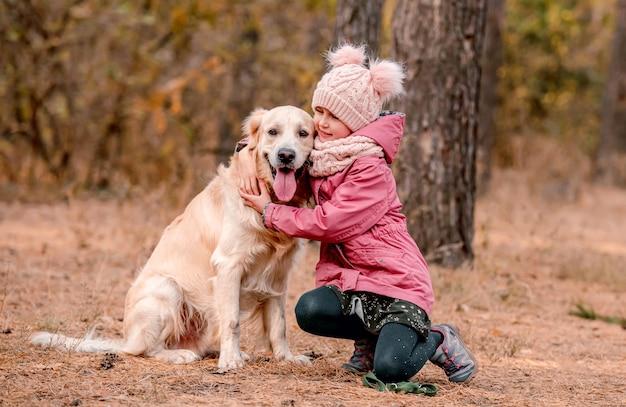 Mała dziewczynka siedzi bokiem, trzymając w rękach smycz golden retrievera w jesiennym lesie