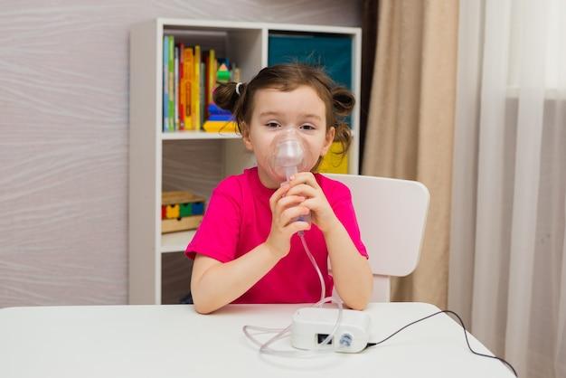Mała dziewczynka siedzi i wykonuje wdech przez nebulizator w pokoju