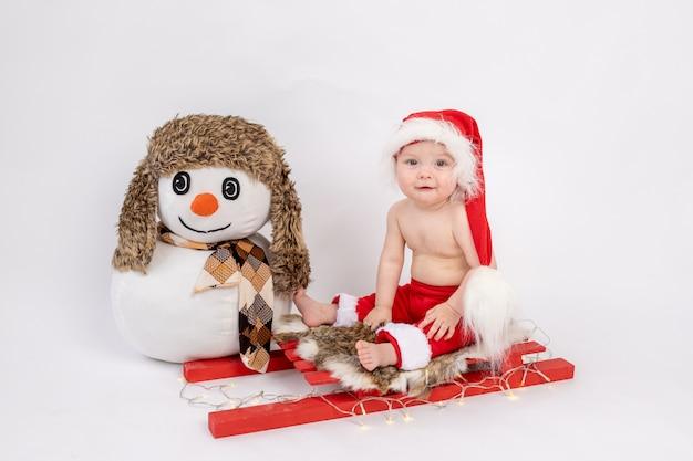 Mała dziewczynka siedzi na czerwonych saniach w kapeluszu santa na białym tle