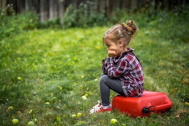 Mała dziewczynka siedzi na czerwonym kanistrze, smutna emocja