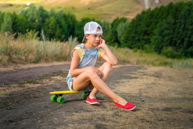Mała dziewczynka siedzi na deskorolce na wsi