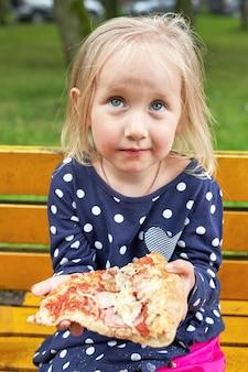 Mała dziewczynka siedzi na drewnianej ławce z dużym kawałkiem pizzy. strzał w pionie