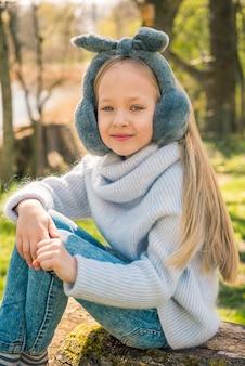 Mała dziewczynka siedzi na dużym pniu w przyrodzie na wiosnę