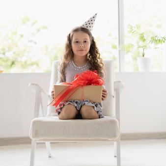 Mała dziewczynka siedzi na fotelu na głowie ma świąteczną czapkę.