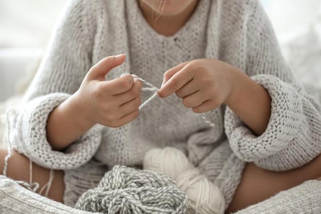 Mała dziewczynka siedzi na kanapie i uczy się robić na drutach, koncepcja wypoczynku w domu.