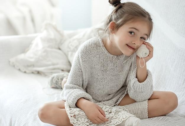 Mała dziewczynka siedzi na kanapie z kłębkiem nici i uczy się robić na drutach.