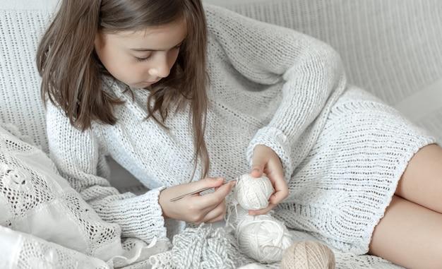Mała dziewczynka siedzi na kanapie z wątków, koncepcja wypoczynku w domu, szydełkowanie.