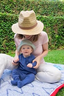 Mała dziewczynka siedzi na kratki z młodą mamą w kapeluszu