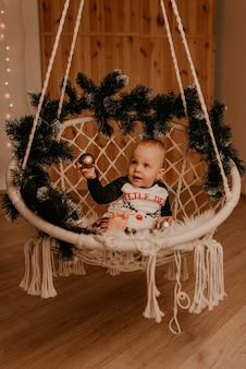 Mała dziewczynka siedzi na krześle i gra. świąteczny poranek. noworoczne wnętrze. obchody walentynek