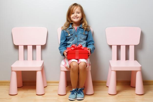 Mała dziewczynka siedzi na krześle i trzyma pudełko z prezentem