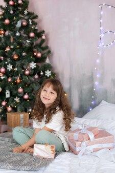 Mała dziewczynka siedzi na łóżku przed choinką w otoczeniu