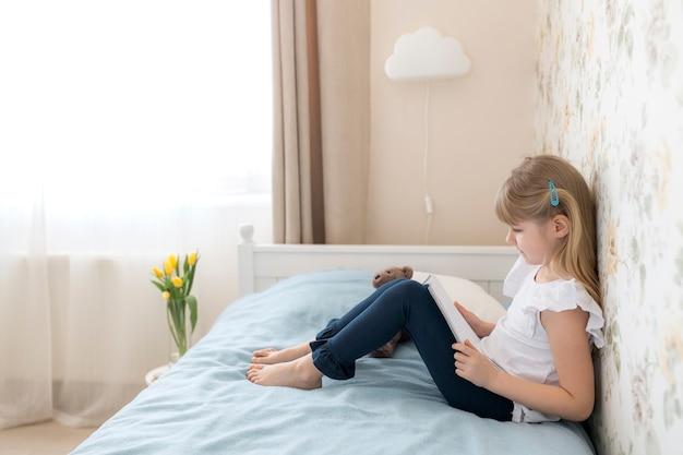 Mała dziewczynka siedzi na łóżku w stylowej sypialni i czyta niebieską książkę. edukacja, koncepcja nauczania w domu. robić prace domową. żółte tulipany w wazonie przy łóżku. kinkiet w chmurze.