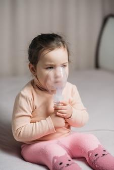 Mała dziewczynka siedzi na łóżku w sypialni z maską tlenową