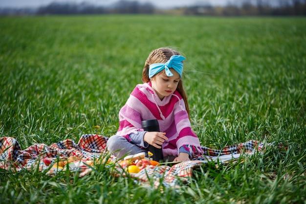 Mała dziewczynka siedzi na narzucie i czyta książkę z bajką, zielona trawa na polu, słoneczna wiosenna pogoda, uśmiech i radość dziecka, błękitne niebo z chmurami