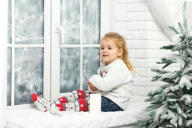 Mała dziewczynka siedzi na parapecie wieczorem przed świętami bożego narodzenia. przytulny romantyczny wypad zimą. wesołych świąt, nowego roku, wakacji, zimy, dzieciństwa