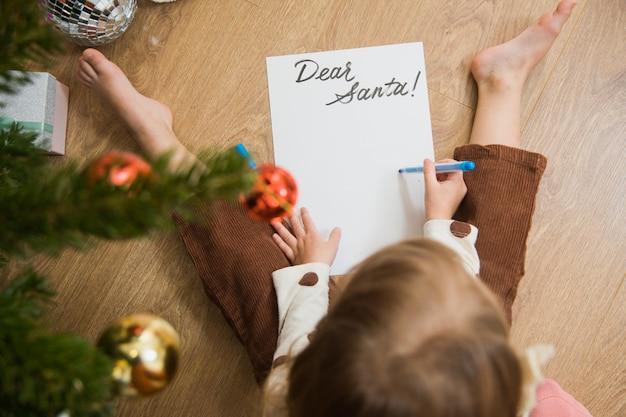 Mała dziewczynka siedzi na podłodze i pisze lub rysuje list dla mikołaja. słodkie dziecko składa życzenia na boże narodzenie w domu.