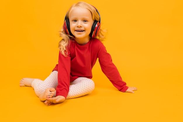 Mała dziewczynka siedzi na podłodze i słuchanie muzyki w słuchawkach na żółtym tle.
