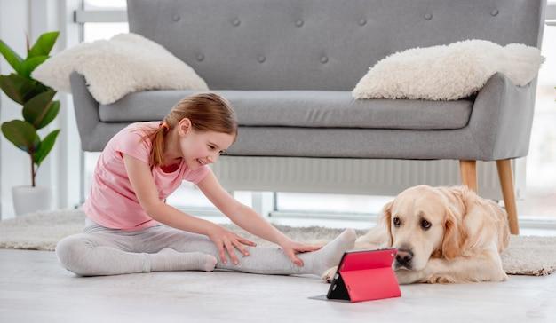 Mała dziewczynka siedzi na podłodze z psem golden retriever i rozprostowuje nogi podczas treningu online z tabletem