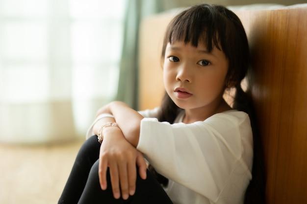 Mała dziewczynka siedzi na podłodze
