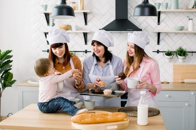 Mała dziewczynka siedzi na stole w kuchni i dobrze się bawi. babcia i jej córki piją kawę i jedzą babeczki. szczęśliwe kobiety w białych fartuchach piec razem. dzień matki