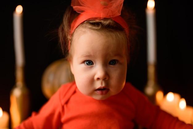 Mała dziewczynka siedzi na tle jack dynie i świece na czarnym tle. zbliżenie.