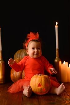Mała dziewczynka siedzi na tle jack dynie i świece na czarnym tle.