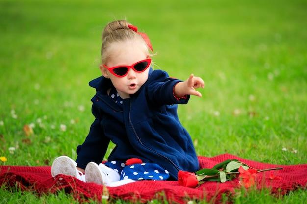 Mała dziewczynka siedzi na trawie w parku w okularach przeciwsłonecznych