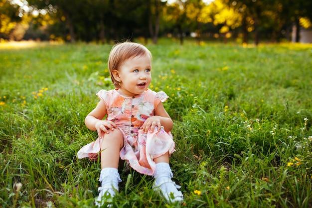 Mała dziewczynka siedzi na trawie.