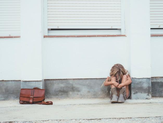 Mała dziewczynka siedzi na ulicy
