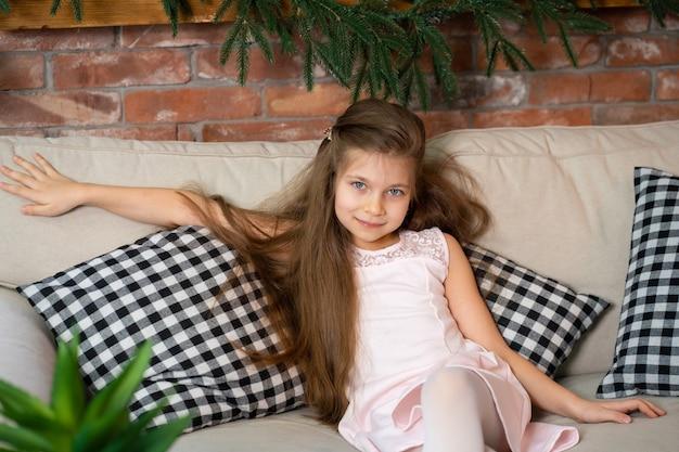 Mała dziewczynka siedzi na wygodnej kanapie z poduszkami w kratkę