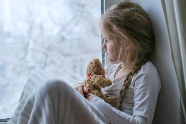 Mała dziewczynka siedzi patrząc przez okno na zimowy krajobraz