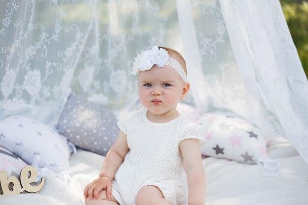 Mała dziewczynka siedzi pod baldachimem na białym kocu w parku. śliczna dziewczyna odwraca wzrok w białej sukni i opasce z natury. mała dziewczynka marszczy brwi