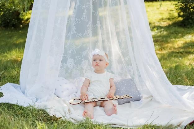 """Mała dziewczynka siedzi pod baldachimem na białym kocu w parku. urocza dziewczyna odwraca wzrok w białej sukni i pałąku z natury. dziewczynka trzyma znak """"szczęście"""""""