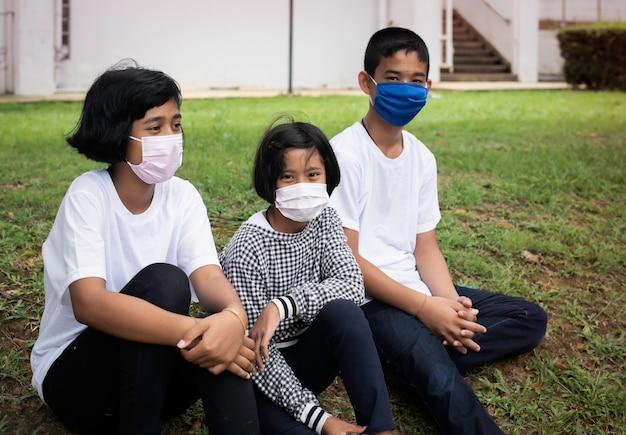 Mała dziewczynka siedzi pośrodku młodszej siostry i jej brata. maluje kolor na płótnie. noszą maski, aby chronić się przed chorobami, nowe normalne życie