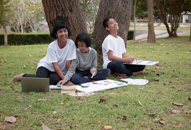 Mała dziewczynka siedzi pośrodku młodszej siostry i jej brata. maluje kolor na płótnie. uśmiechają się radośnie, wykonują razem aktywność w parku