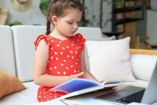 Mała dziewczynka siedzi przy desl w domu i odrabia pracę domową, samodzielną naukę materiału, czytanie książki. pojęcie kształcenia na odległość.