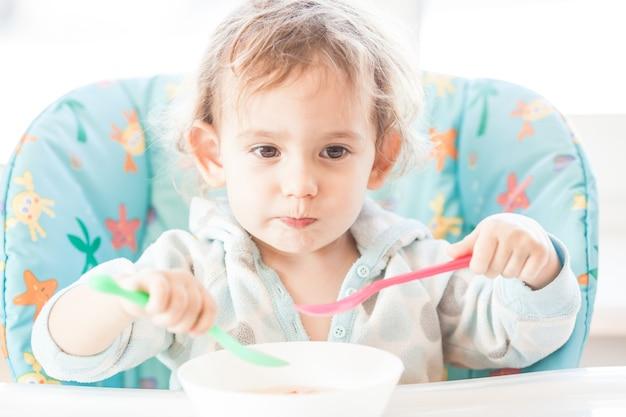 Mała dziewczynka siedzi przy stole i je dwiema łyżkami. pojęcie super wydajności