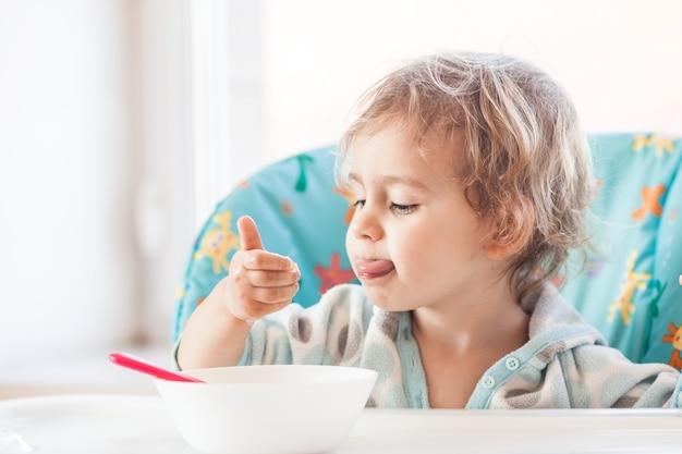 Mała dziewczynka siedzi przy stole i je łyżką