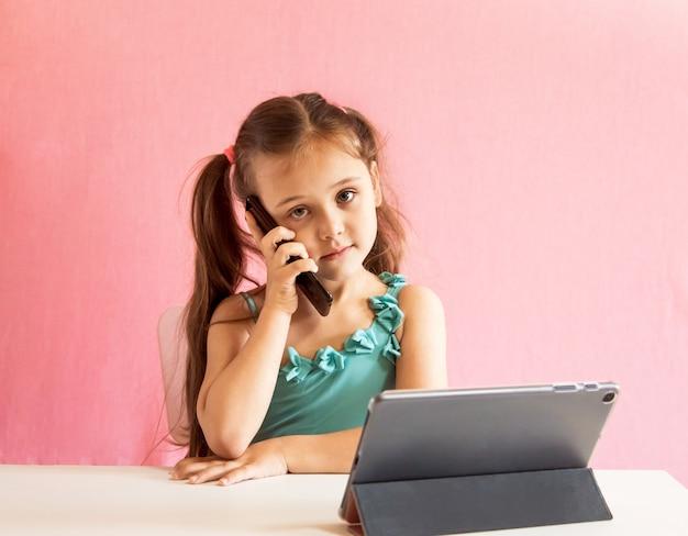 Mała dziewczynka siedzi przy stole i rozmawia przez telefon