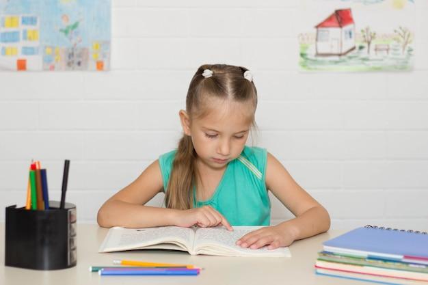 Mała dziewczynka siedzi przy stole i uczy się czytać podręcznik