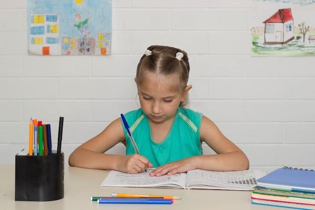 Mała dziewczynka siedzi przy stole i uczy się pisać